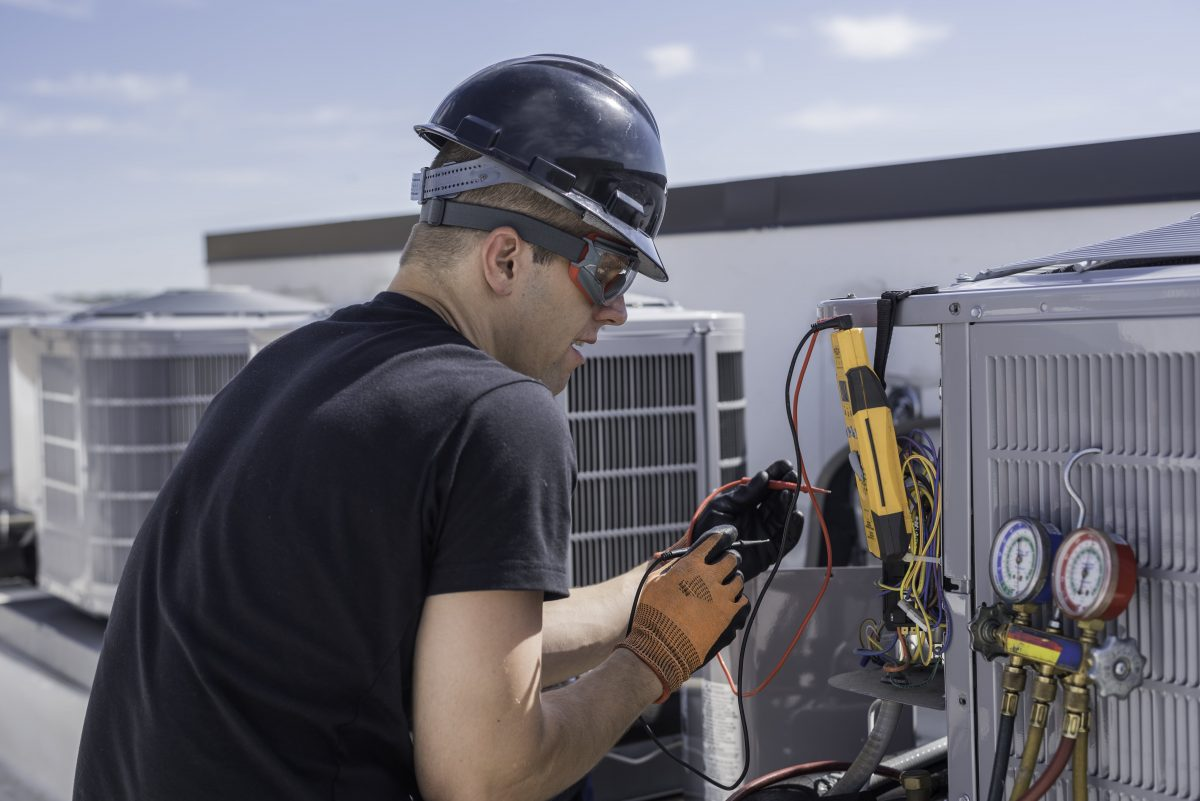 hvac technician working on a rooftop unit in st louis mo